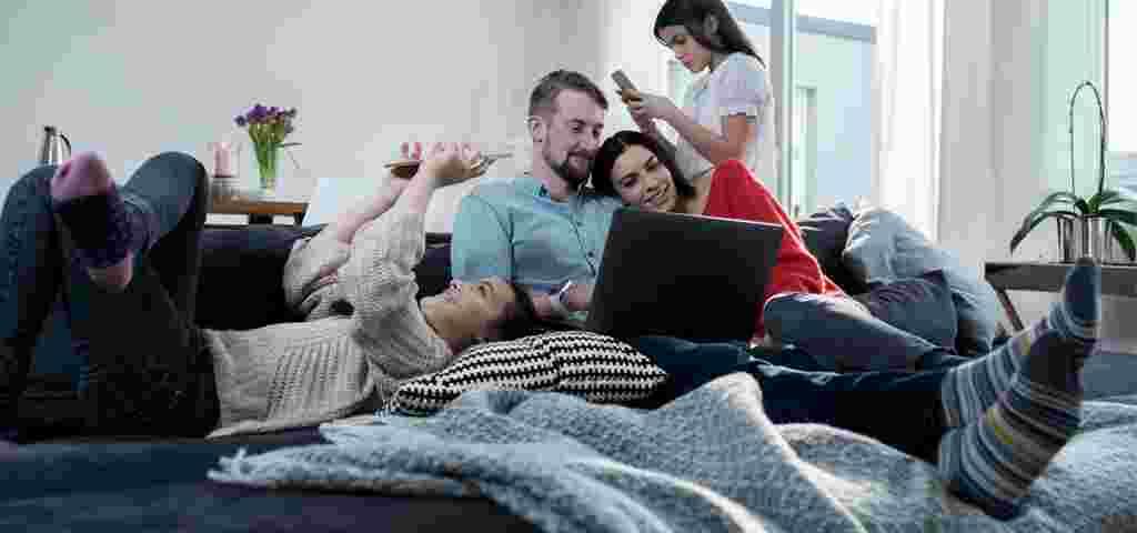 Familie i sofaen med mobiler og bærbar PC