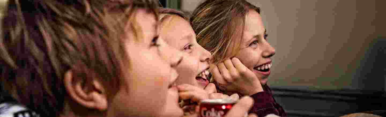 Smilende barn i profil, de ser trolig på TV