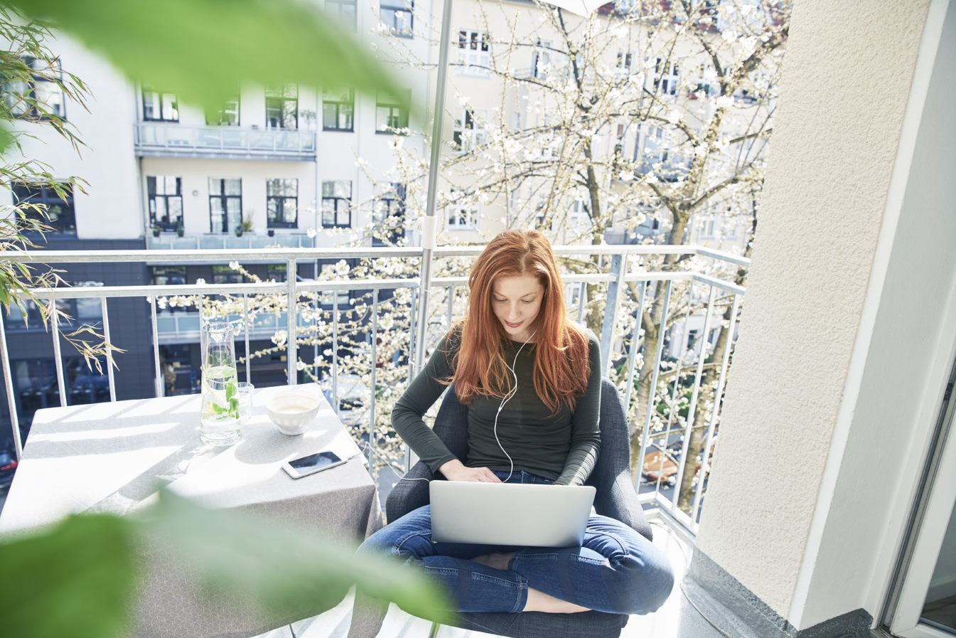 A redhaired girl sits on a balcony with her laptop in her lap.
